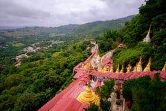 View of buddhist gold pagodas and colorful staircase to Pindaya. Caves, Myanmar Burma Stock Photos