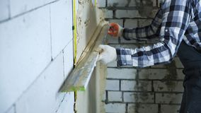 View of builder hands in gloves using construction ruler for plastering royalty free stock photos