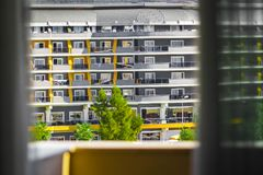 View of building from the balcony. View of modern contemporary colorful building and green trees from the balcony with grey thready curtains Royalty Free Stock Photography