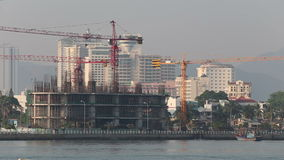 View of building construction with cranes on embankment. Panorama of building construction with cranes on embankment in Vietnam resort city at dawn stock footage