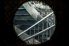 View through a Bullauge into a staircase with 2 opposing curved stainless steel stairs and stainless steel railing Royalty Free Stock Images