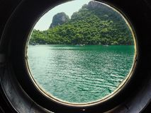 View through a bulls-eye window in ship with island outside royalty free stock photo
