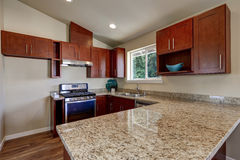 View of burgundy kitchen cabinets with granite counter top. And dining area. House interior. Northwest, USA stock photos