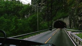View of bus drive from one dark tunnel to another one on road in mountains. Green trees. Rain. Camera inside driver cabin stock footage