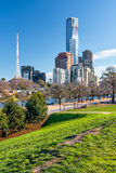 View of the business district and the TV tower in Melbourne. Australia. The river and park with alley and benches in the foreground. Green grass on the lawn stock photography