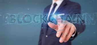 Businessman holding a Blockchain title isolated on a background. View of a Businessman holding a Blockchain title isolated on a background Royalty Free Stock Photography