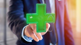 Businessman holding a Lighting pharmacy cross and a stethoscope. View of a Businessman holding a Lighting pharmacy cross and a stethoscope - 3d render Stock Image