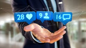 Businessman holding a Like, Follower and message notification on. View of a Businessman holding a Like, Follower and message notification on social network - 3d Royalty Free Stock Photo