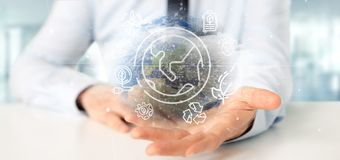 Businessman holding a World globe surronding by ecology icons an. View of a Businessman holding a World globe surronding by ecology icons and connection 3d stock images