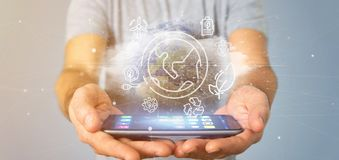 Businessman holding a World globe surronding by ecology icons and connection 3d rendering. View of a Businessman holding a World globe surronding by ecology stock image