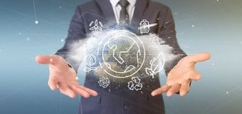 Businessman holding a World globe surronding by ecology icons and connection 3d rendering. View of a Businessman holding a World globe surronding by ecology royalty free stock photo