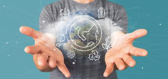Businessman holding a World globe surronding by ecology icons an. View of a Businessman holding a World globe surronding by ecology icons and connection 3d stock photo