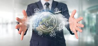 Businessman holding a World globe surronding by ecology icons an. View of a Businessman holding a World globe surronding by ecology icons and connection 3d stock photography
