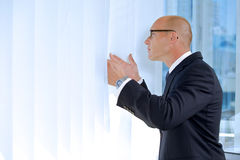 View of businessman looking through window Stock Photo