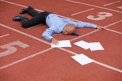 View of a businessman lying on a race track Royalty Free Stock Photography
