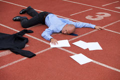 View of a businessman lying on a race track Royalty Free Stock Photos