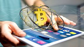 Businessman using a smartphone with a Bitcoin crypto currency si. View of a Businessman using a smartphone with a Bitcoin crypto currency sign flying around a Stock Photos