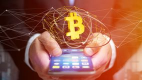 Businessman using a smartphone with a Bitcoin crypto currency si. View of a Businessman using a smartphone with a Bitcoin crypto currency sign flying around a Royalty Free Stock Images