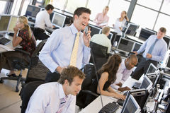 View Of Busy Stock Traders Office. With A Man On The Phone Standing And Laughing Royalty Free Stock Photos