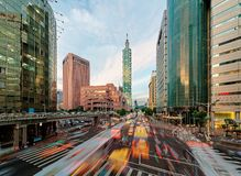 View of a busy street corner at rush hour in Taipei, the capital city of Taiwan. With cars and buses dashing through the intersection, Taipei 101 Tower & World Royalty Free Stock Photography