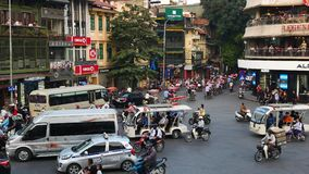 View of busy traffic in an intersection with many motorbikes and vehicles in Hanoi, capital of Vietnam.