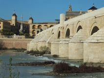 View of Córdoba's Roman Bridge from the south bank of the Guadalquivir river. With the Mosque-Cathedral in the background stock images