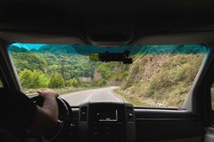 View from the shuttle bus to the mountain road. View from the cab of route transport to the mountain serpentine and forests in the gorge where the road passes Royalty Free Stock Photos