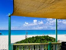 View from cabin of beach with turquoise water in Grace Bay, Prov. Idenciales, Turks and Caicos. Canvas cover on green structure Royalty Free Stock Photography