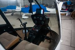 A view through the cabin of a small helicopter to the covered sports airplanes in the hangar Royalty Free Stock Photography