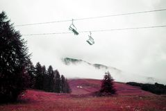 A view of cable cars, landscape, mountains and fog in the alps switzerland in winter in color infrared.  Stock Photo
