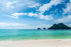 View of the calm azure sea, green mountain and beautiful clouds. In Thailand Stock Photography