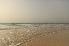 View on the calm sea from an empty sandy beach at sunset. Dubai Royalty Free Stock Photos