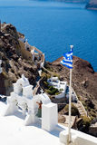 View on calm sea surface through traditional Greek white church arch. With cross and bells in village Oia of Cyclades Island Santorini Greece Royalty Free Stock Photo