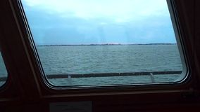View of calm turquoise sea and coast through window of ship. Clear day. stock footage
