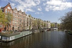 Canal with house boats in Amsterdam. A view of a canal with house boats moored on the shore in Amsterdam, Netherlands royalty free stock photo