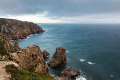 View from Cape Roca in Portugal: the Atlantic Ocean and rocks in front of the sunset Royalty Free Stock Images