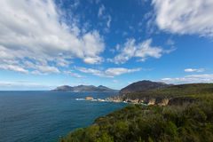 View from Cape Tourville Lighthouse lookout, Freycinet National. View from Cape Tourville Lighthouse lookout - Seascape photo, cliff coastline, green mountain Stock Photo