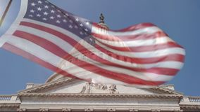 View of the Capitol Building dome in Washington DC with a blillowing US flag. The Capitol Building dome in Washington DC with a billowing US flag in front.  4k stock video footage