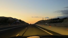 View from car cabin in twilight. View from driving car. Shooting from cabin of auto. The way to the city. Cars drives on the road in twilight at the finish of stock video footage