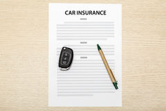 View of car keys and pen laying on a blank of insurance. Stock Photography