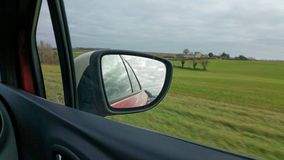 View from car. Looking at and into rear view wing mirror of red vehicle Stock Image
