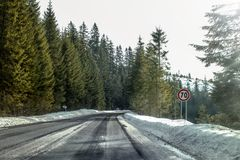 View from a car riding through road curve in winter. With 70 speed limit on the right - dangerous driving conditions Stock Image