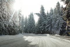 View from a car riding through snow covered winter road curve. Lit by strong sun backlight - dangerous driving conditions Stock Photo