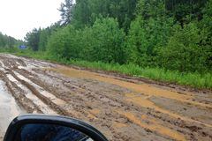View from the car on the terrible country dirt road with puddles and mud surrounded by green forest royalty free stock images