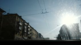 View from the car to the city. Focus on the dirty windshield. The car is in motion. View from the car to the city. Focus on the dirty windshield. The car is in stock footage
