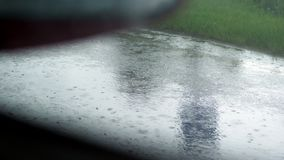 View from the car window. close-up, edge of the road, roadside, in the rain., while the car is moving. view from the car stock video