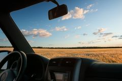 View from car window on the field at sunset Royalty Free Stock Images