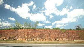 View from car window of road and countryside, with blue sky and clouds in background stock video
