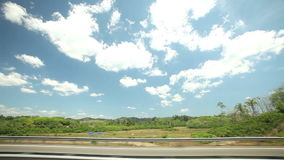 View from car window of road and countryside, with blue sky and clouds in background stock footage