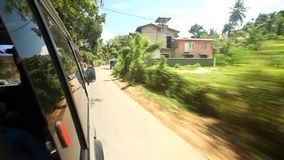 View from car window of road and countryside village, with blue sky and clouds in background stock footage
